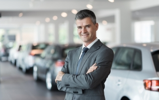 Confident smiling car salesman at the showroom, he is standing with arms crossed, luxury cars on the background